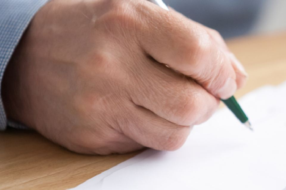 view of a hand holding a pen over a piece of paper
